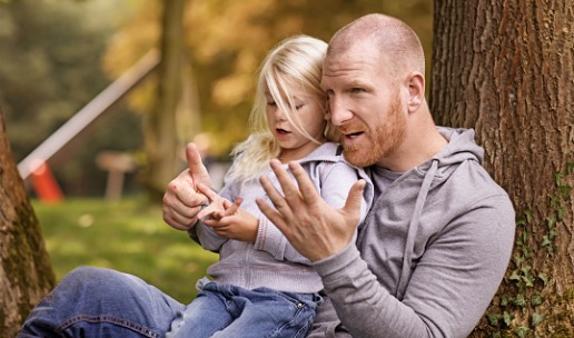 A daughter sits in her father's lap as they sit leaning against a tree outside, counting on their fingers together.