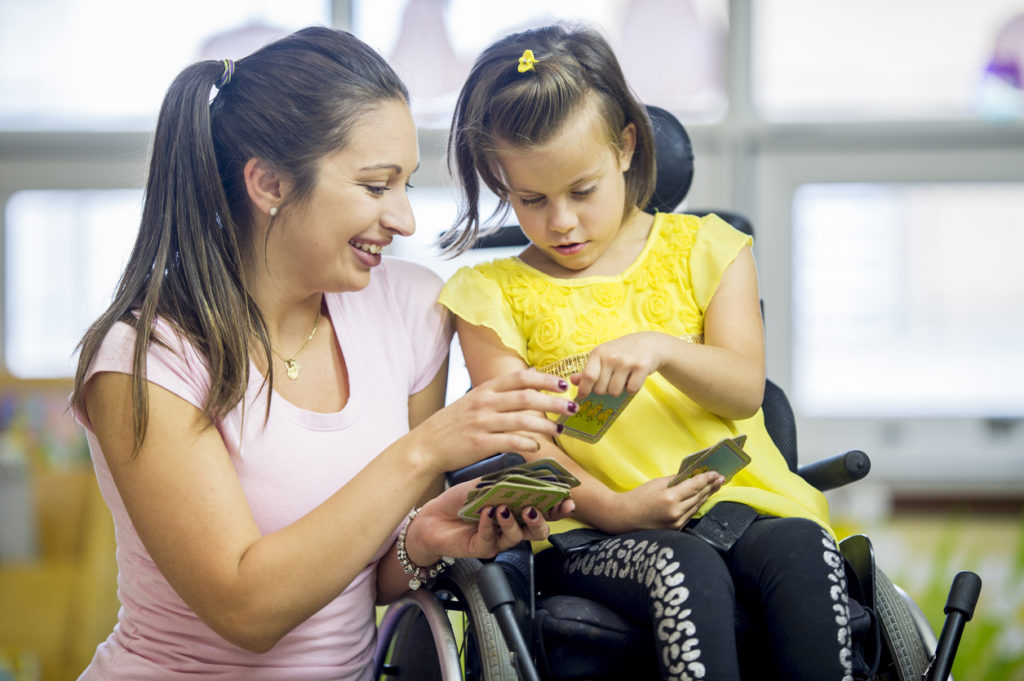 a mom kneels next to her daughter who is in a wheelchair and they flip through cards together.