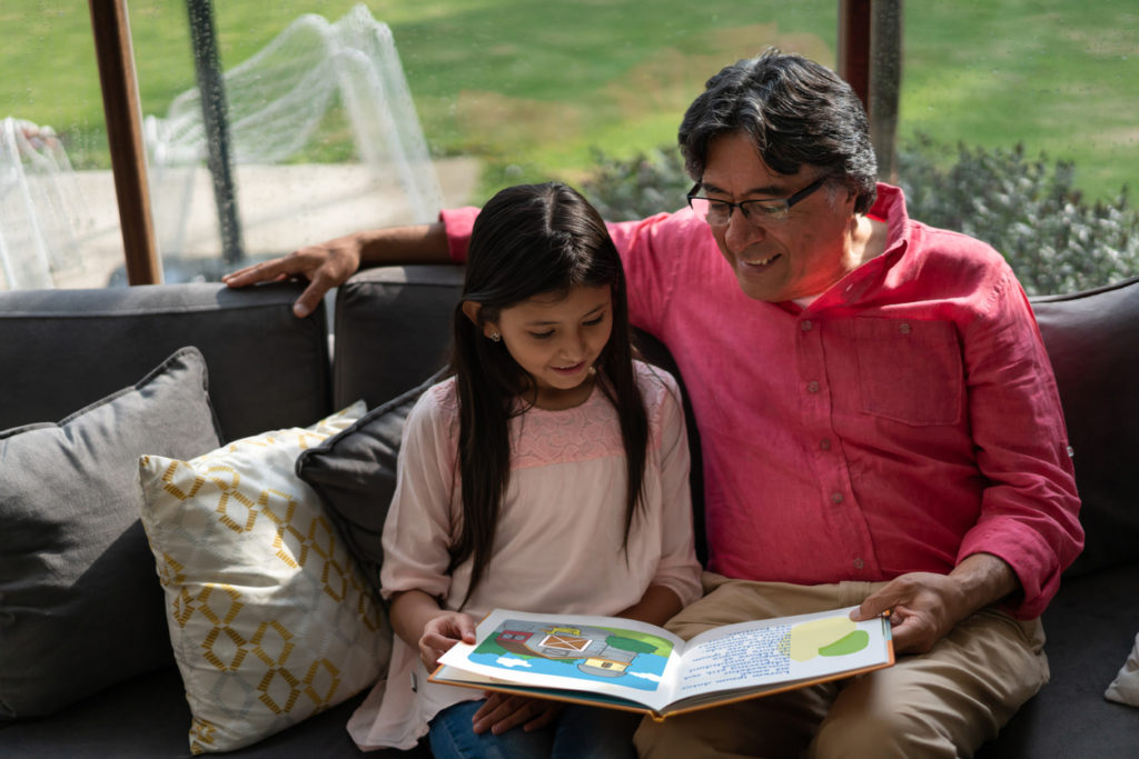 A grandfather and granddaughter sit on a couch reading a book, with the grandfather's arm around his daughter.
